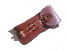 A curvaceous 4-5 oz. leather case. Decked with latigo lacing and wooden beads, this case is durable and accommodating. Opens up easily, just pull
