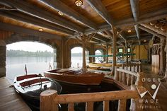 roger wade studio architectural photography of handcrafted log boat house with old wooden boats looking out to upper st. regis lake, paul smiths, new york, by maple island log homes