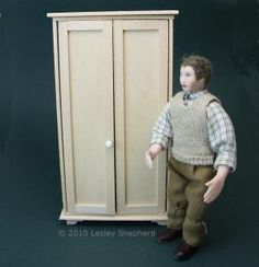 A simply constructed dolls house scale armoire with shaker doors is shown beside a doll for scale - Photo copyright 2010 Lesley Shepherd, Licensed to About.com Inc.