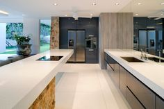 White countertops and matching floor brightens this open kitchen, along with stone island and wall accents, with wall-size mirror on right.