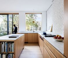 Kitchen, Medium Hardwood Floor, Wood Cabinet, Pendant Lighting, Drop In Sink, Cooktops, Brick Backsplashe, and Marble Counter American white oak was used for the flooring throughout the house, including the sun-filled kitchen. A Brendan Ravenhill hangs above the sink, and a Wolf cooktop was installed opposite the island.