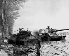 A German paratrooper walks past a pair of destroyed tanks.