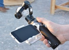 DJI Inspire 1 Handheld Camera Gimbal Prototype Unveiled - The DJI Inspire 1 handheld camera gimbal allows users to stream the imagery from the small gimballed camera in front directly to their smartphone, which is also used as a viewing screen whilst recording and held in place via the integrated smartphone mount.   Geeky Gadgets