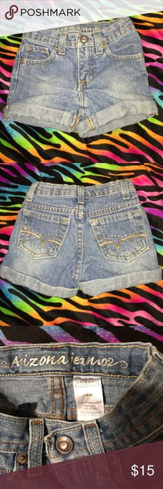 Girls rolled cuff Arizona jean shorts 4 SLIM Girls rolled cuff Arizona jean shorts size 4 slim. Adjustable waist. Zip fly and snap closure with rhinestone center. Tan and brown stitching and rhinestones on back pockets. Medium stonewash color. In excellent used condition. 100% cotton Arizona Jean Company Bottoms Shorts
