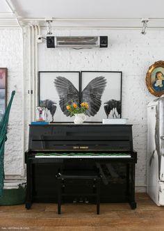 Parede de tijolinho, piano e quadros na sala de estar dessa casa em SP.