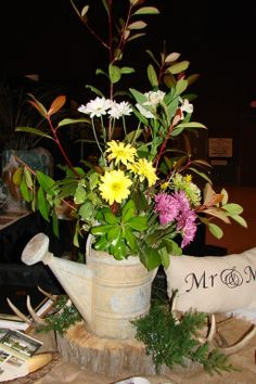 Old metal watering can filled with greenery and fresh flowers, sitting atop tree disk, burlap, and deer antler