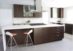 kitchen modern with brown wood cabinets stove hood above kitchen island
