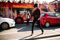 Street Style: Milan Fashion Week Spring 2017: Red and Black Striped One Shoulder Top, Black Purse with Gold Chain, Red High Heels, Cityseeing Bus | coveteur.com
