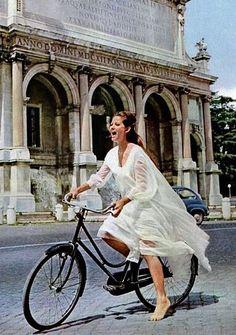 Claudia Cardinale rides a bike.