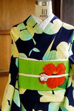 濃紺の地に、シャーベットのような澄んだイエローやグリーン、ブルーやピンクの綺麗色も印象的に、夢二の挿絵を思わせるような愛らしい椿模様が染め出された注染レトロ浴衣です。