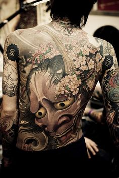 Looks a bit like a traditional Japanese styled back piece, with the main art being based upon an oni mask, and sakura blossoms... Very pretty, swirly and just a little bit frightening, as it should be. :)