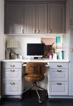 gray cabinets and brass hardware make up a practical builtin home office