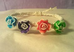 This handmade bracelet is made from natural hemp, with four polymer rose beads in blue, purple, orange and green. Each rose bead measures