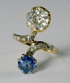 Circa early 20th century. An 18ct gold, diamond and sapphire cross-over ring