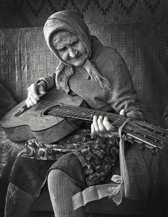this photo shows that no matter what music will always be a part of someones life. this woman has played the guitar her whole life and eve though she is near her death bed she still plays her guitar