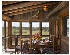 This Rustic Porch Dining area has all the right touches, from the antlers to the sunflowers!