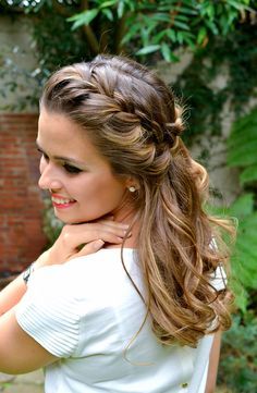 A deep side part with a braid and two loose twists cascading back into a curly bun is a great hairstyle for the bride!