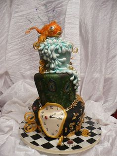 Whimsical topsy-turvy wedding cake with goldfish, peacock feathers and Dali-esque melting clock.