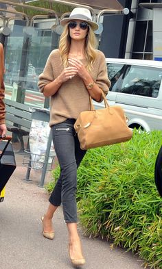 Rosie Huntington-Whiteley at Nice airport in skinny Isabel Marant trews, a roomy sweater by The Row, nude heels, a Maison Michel fedora hat and a lust-worthy Balmain bag.