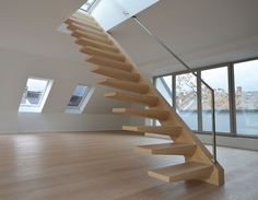 Treppenbau DIEHL | Freistehende Kragarmtreppe mit Edelstahlhandlauf  Besonders auffällig an dieser freistehend in der Raummitte angebrachten Treppenanlage ist die ungewöhnliche Form der Befestigung für die Trittstufen. Denn es ist unüblich, bei einer freistehenden Treppe die Stufen nur einseitig zu befestigen.