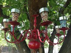 DIY colorful Outdoor lighted chandelier. Found brass chandelier road side, spray painted red and added solar lantern yard stakes.