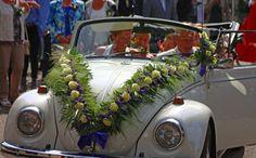 Volkswagen kever met een guirlande opgebonden met Avalanche rozen van Meijer Roses, paarse Statice en gras.