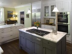 Cabinetry : Paint finish in Benjamin Moore Moonlight White, island in custom blue-gray glaze, by Downsview Kitchens  Wall Color: Rice Paddy by Benjamin Moore  Counter tops & Back Splash: Calacatta Gold from Art Rock Creations