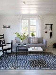 Vardagsrummet går i vitt, grått och blått. De vackra gamla fönstren blir som ett smycke. Matta, House Doctor.