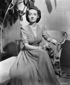 American actress Bette Davis wearing a long chiffon dress sits on a basket table…