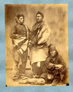 Photograph (black and white); studio portrait of three Pawnee men, from left to right; the first man is standing wearing a military coat, trousers, shoes, a blanket around his waist, and a head scarf around his head; the second man is standing wearing a military coat, trousers, shell ear ornaments, and a hide robe; the third man is seated wearing a cloth shirt, leggings, moccasins, a blanket around his waist and a cloth cap; Omaha, United States of America Albumen print