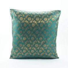 A Pillow made of a Dark Bluish/Teal green Brocade,Featuring a Rich floral pattern in brocade style gold weave,The golden weave is down by luxurious