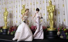 Jennifer Lawrence and Anne Hathaway hold their Oscars for Best Actress and Best Supporting Actress respectively
