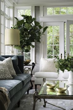 Classic green, white and gray living room filled with plants and floor-to-ceiling paneled windows.