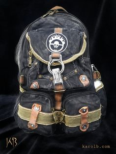 The War Boy backpack features an Immortan Joe logo patch. The backpack is 100% cotton black canvas, with distressed vintage military-style hardware. 7 pockets in all - 4 with zippers. Measures approximately 18 tall, and 13 wide. Canteen not included.