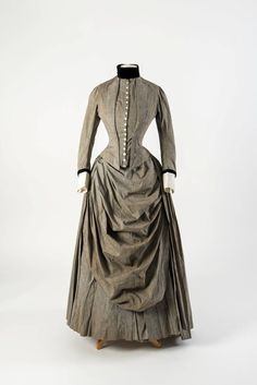 grey cotton dress with draped apron front & black velvet trimming at collar & cuffs, late 1880s