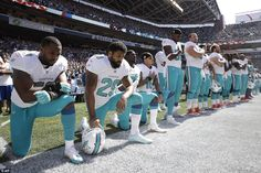 From left, Miami Dolphins' Jelani Jenkins, Arian Foster, Michael Thomas, and Kenny Stills, kneel during the singing of the national anthem before their game against the Seattle Seahawks on Sunday afternoon on the 15th anniversary of 9/11
