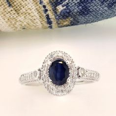 """The """"Bluesette"""" engagement ring features a white diamond halo with an oval shaped, blue sapphire center stone. Inspired by Princess Diana's regal halo, sapphire engagement ring! Sapphire Wedding Rings, Princess Diana, Halo Diamond, Blue Sapphire, White Gold, Engagement Rings, Inspired, Stone, Jewelry"""