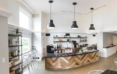 Subway tile and crown molding—all in white, plus the walls and ceiling—make the salvaged-wood design in front of the bar pop even more at Heartwood Coffee Roastery's sole cafe.