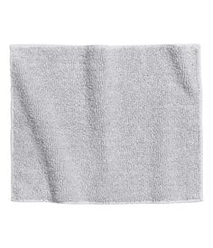 Light gray. Bath mat in thick cotton terry with taped trim.