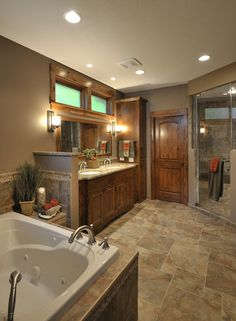 BATHROOM – Warm woodwork in Minnesota. Mixing up the tile size on this bathroom floor makes for an eye-catching design with only a single material. Houzzers also noted the rich wood cabinets and bathroom door when saving this photo to their ideabooks.