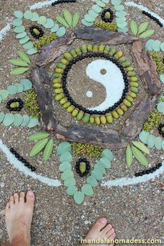 Yin and Yang mandala with barefeet on soft creek bed sand.