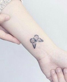 Tiny beautiful grey butterfly wrist tattoo.