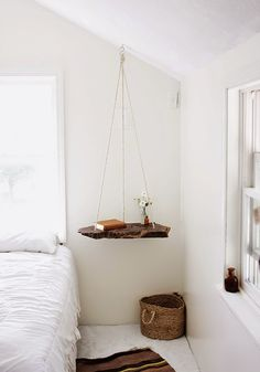 A floating bedside table creates an illusion of more space and gives the room a touch of the wood element.