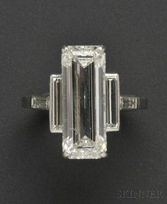 Platinum and Diamond Ring, Cartier, set with an emerald-cut diamond measuring approx. 18.90 x 7.20 x 5.30 mm, and weighing approx. 7.75 cts., flanked by baguette-cut diamonds