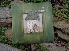 zelený dřevěný obrázek s keramickým domem