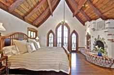 The master suite features a beamed cathedral ceiling, detailed lead glass windows and door leading to the deck, hardwood flooring, and a fireplace.