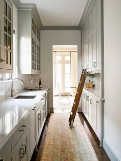 A pink and gold runner covers the floors of this stunning light gray galley style butler pantry fitted with light gray cabinets donning polished nickel pulls and a white quartz countertop fitted with a sink and polished nickel faucet fixed beneath a window flanked by stacked glass front cabinets.