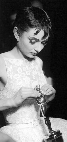"Audrey Hepburn looking down at the Best Actress Oscar on her lap awarded for her role in ""Roman Holiday"" during Academy Awards, 1953."