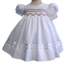 Our precious Charlotte, white 100% cotton girls dress has red rosebuds across the smocked bodice. The sleeves and skirt are trimmed with white satin ribbon, and cotton lace. A sash tied into a bow fin