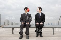 Businessmen wearing masks sat on a bench royalty-free stock photo